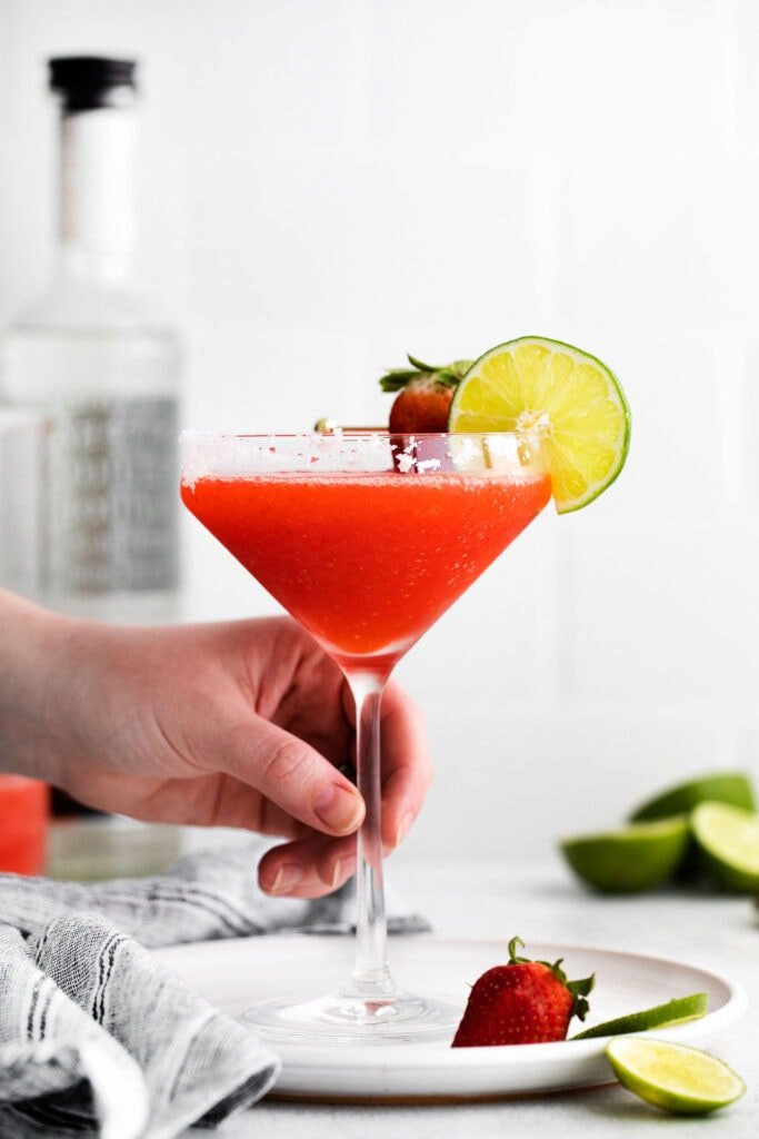 hand holding strawberry margarita in glass