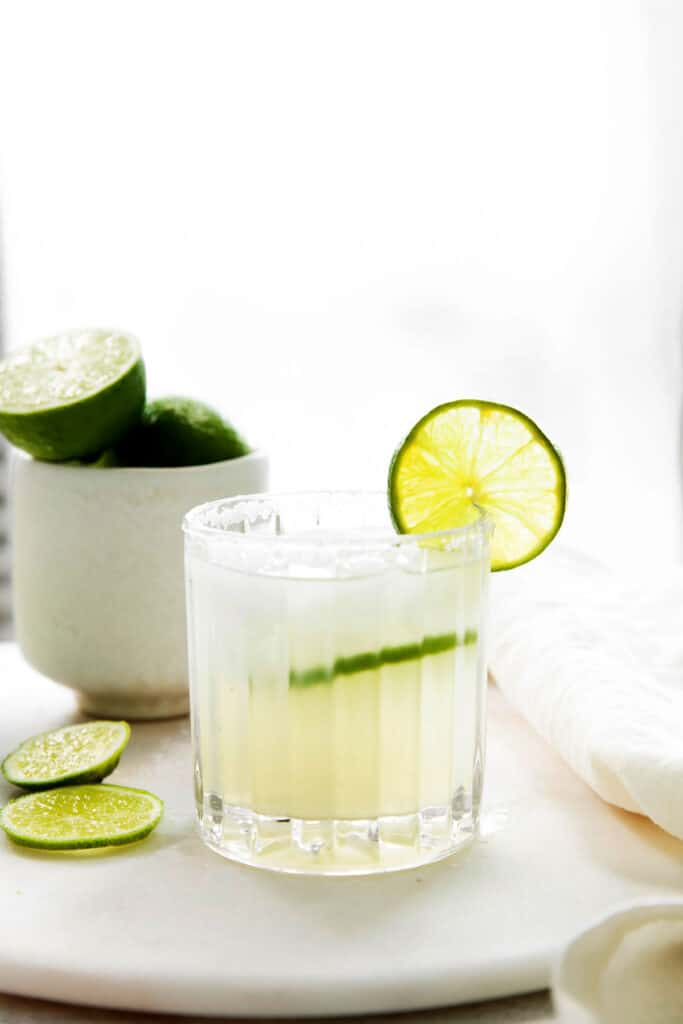 A cocktail glass full of margarita with a fresh lime slice.