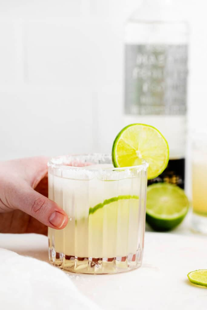 A glass of margarita with a fresh lime slices on the glass.