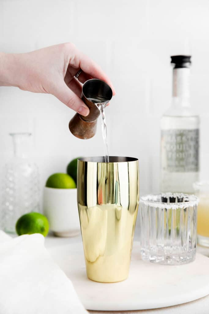 Tequila being poured into a cocktail shaker
