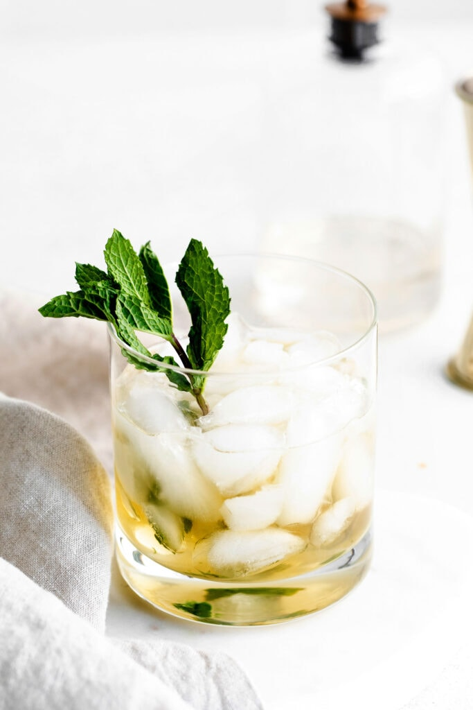 mint julep in a low ball glass garnished with fresh mint