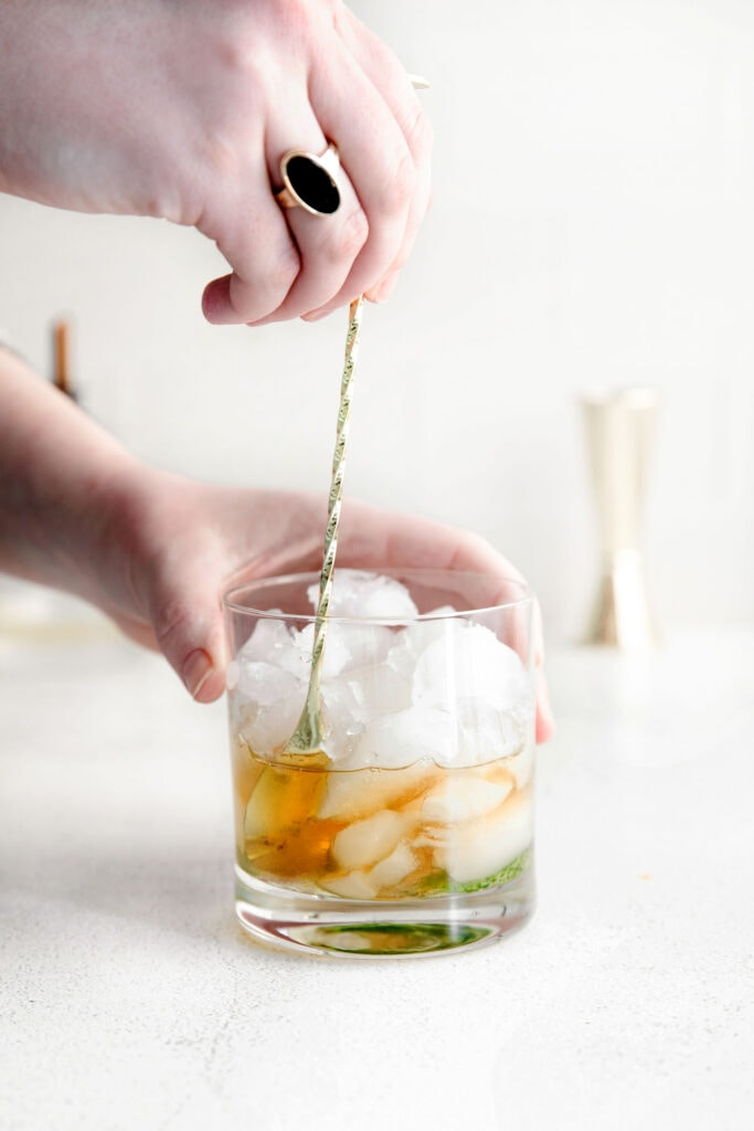 bourbon being stirred into a glass of ice with muddled mint for a mint julep