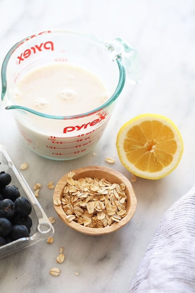 almond milk, rolled oats, lemon, and blueberries on countertop
