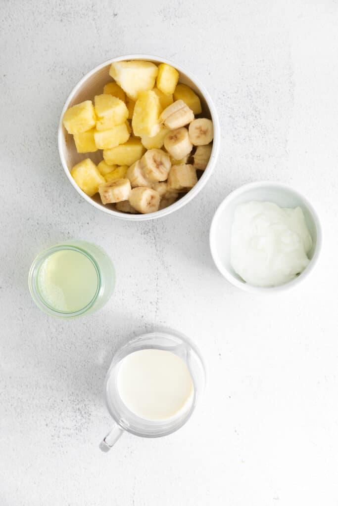 pineapple, banana, Greek yogurt, pineapple juice, and almond milk on countertop