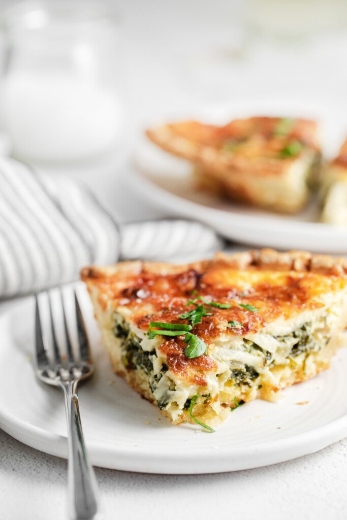 A slice of quiche on a plate.