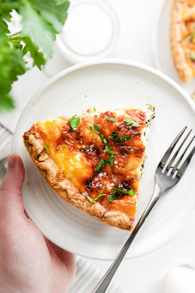 A piece of quiche on a plate.