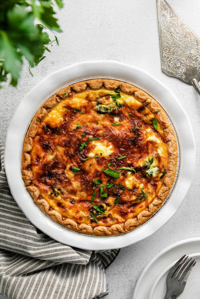A baked spinach quiche with parsley sprinkled on top.