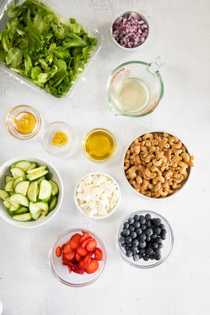 All of the ingredients for a spring mix salad in small bowls.