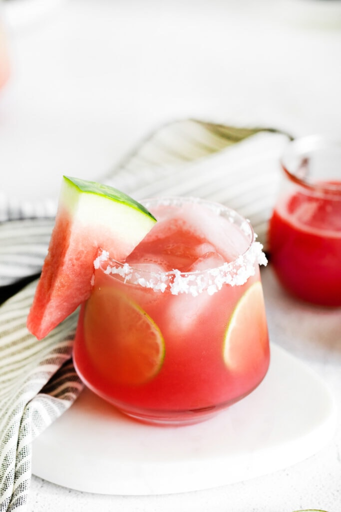 Watermelon margarita in a glass with a salted rim, lime rounds, and fresh watermelon.