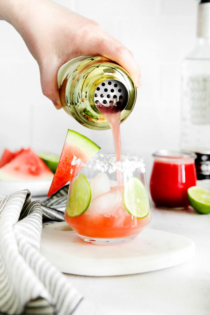 Pouring the watermelon margarita on the rocks.