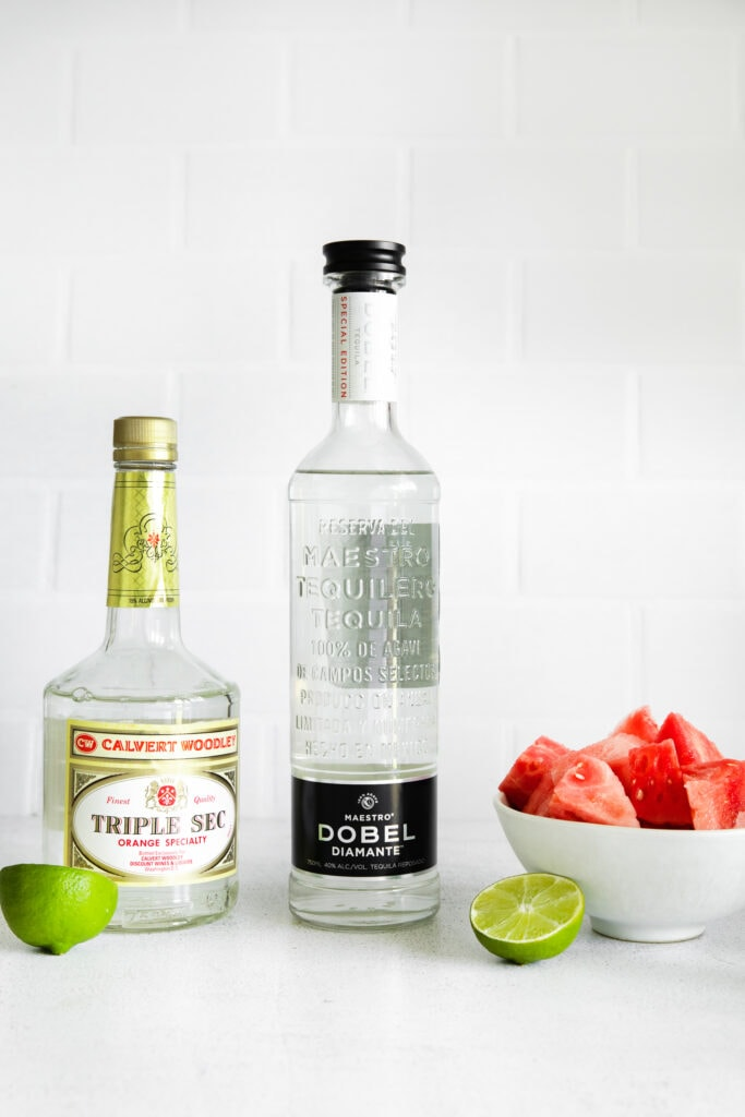 Triple Sec, tequila, fresh watermelon and lime wedges on a counter top.