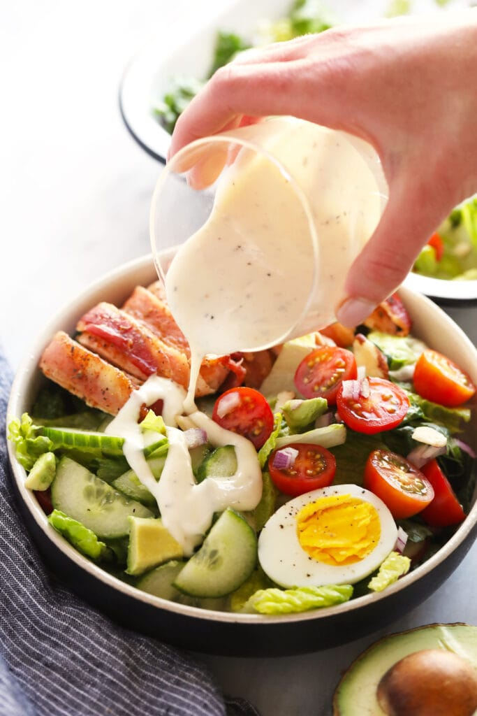 pouring dressing onto salad