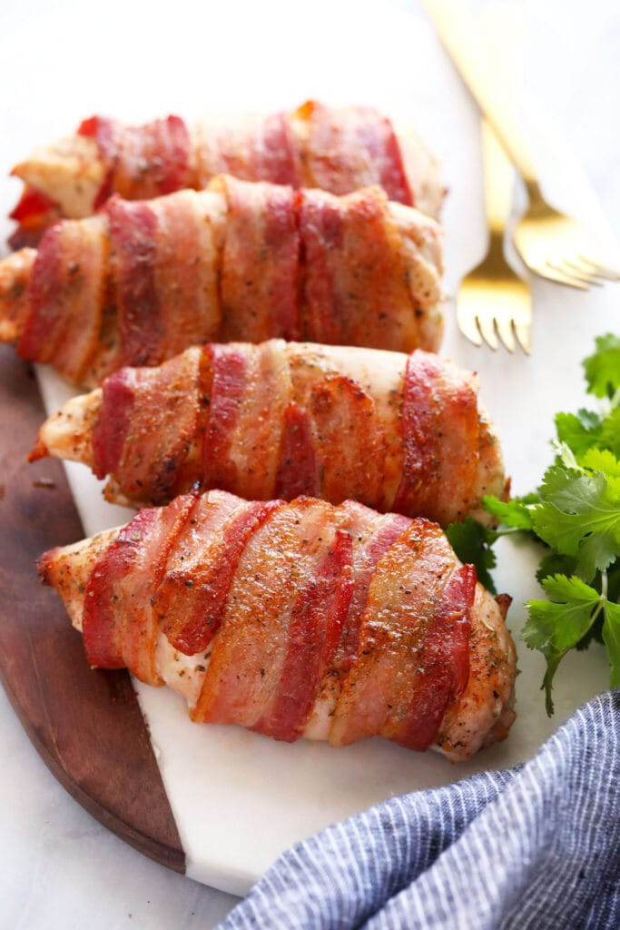 bacon wrapped chicken on cutting bo