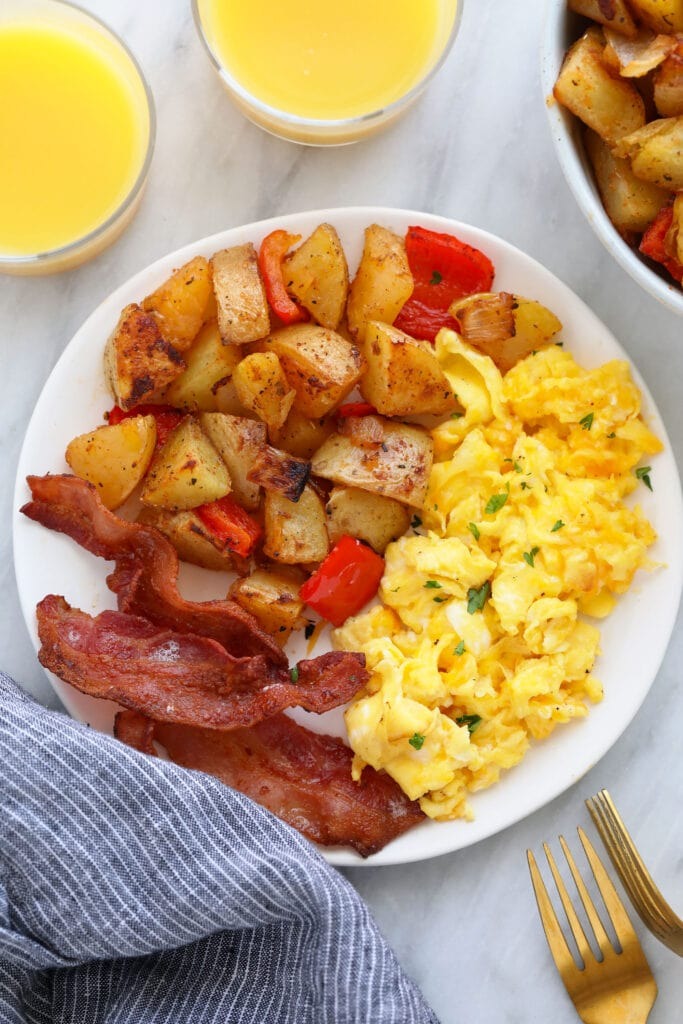 the best breakfast potatoes on a plate with eggs and bacon
