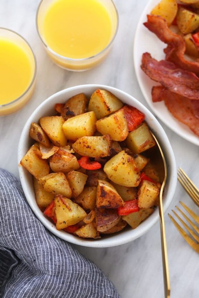breakfast potatoes in a bowl, served next to a glass of orange juice