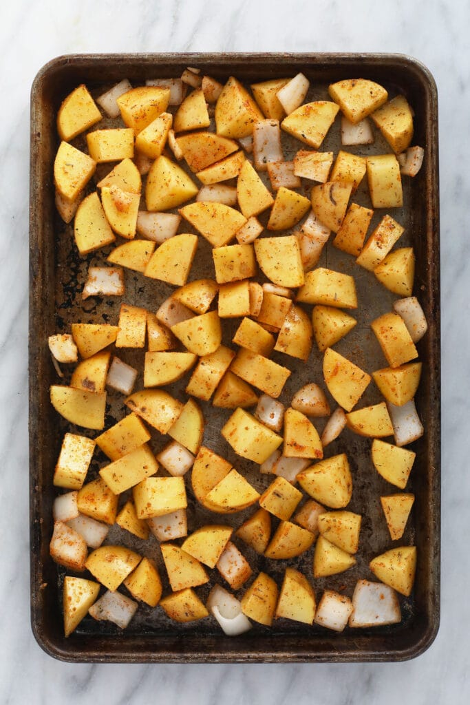 sliced breakfast potatoes on a baking sheet, ready to be baked