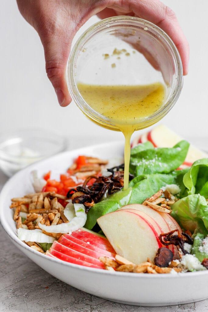 Pouring lemon vinaigrette over the butter lettuce salad