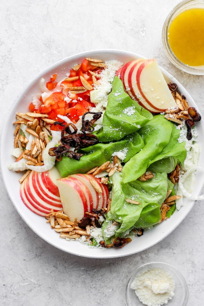 Butter lettuce salad with apples, peppers, slivered almonds, grated parmesan, and more in a salad bowl.