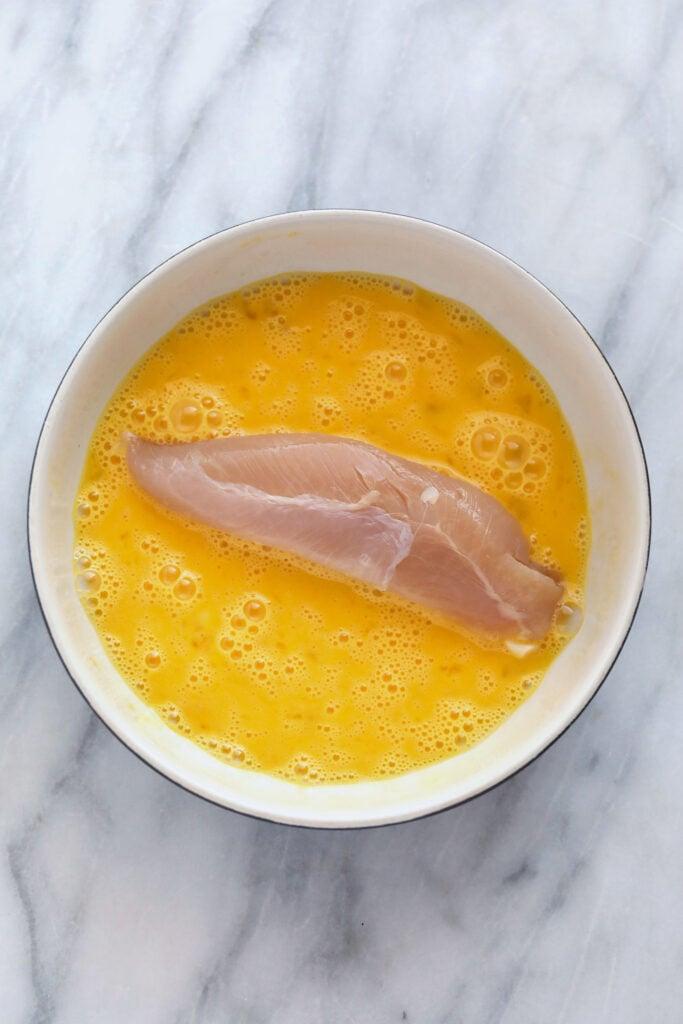 Chicken tender in an egg mixture.