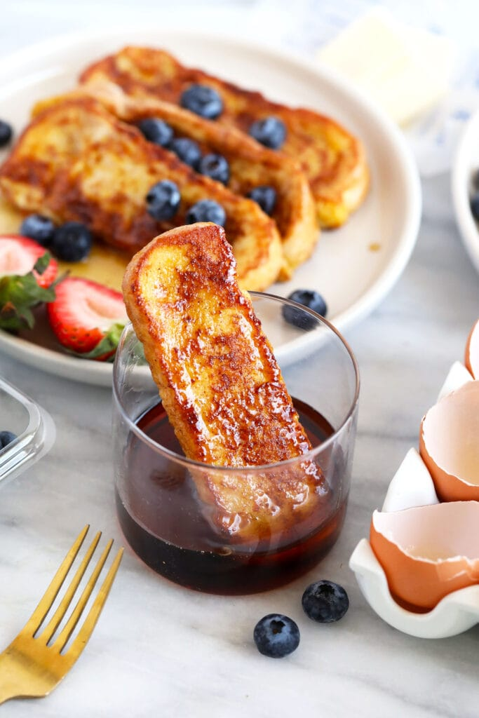 french toast stick in a cup of maple syrup