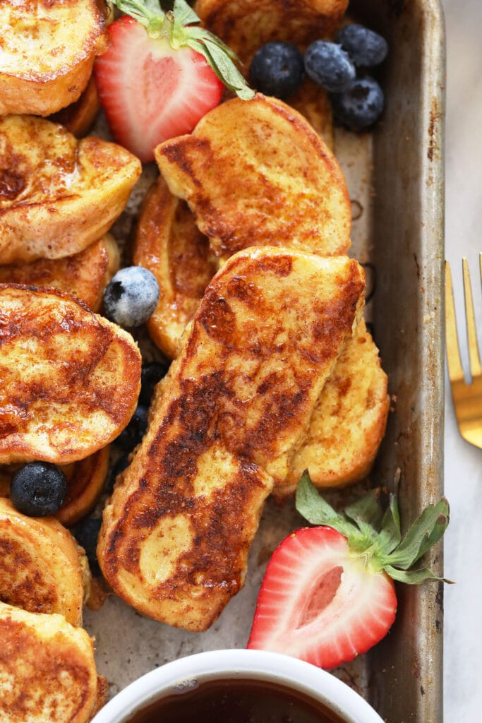 French toast sticks on a baking sheet with strawberries