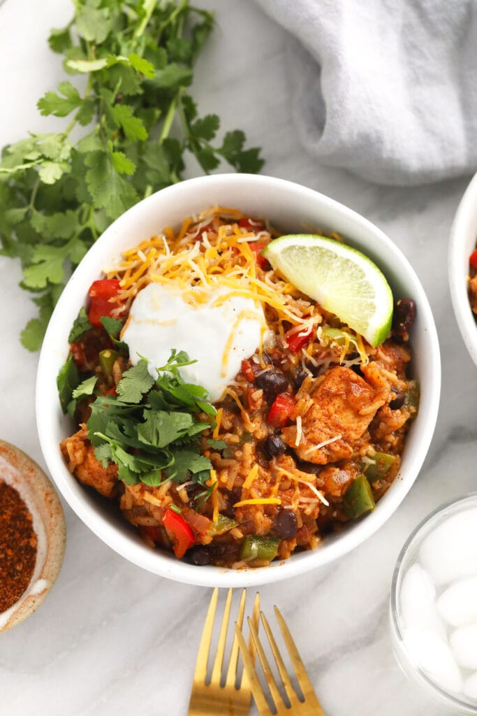 instant pot burrito bowl topped with shredded cheese and greek yogurt and cilantro
