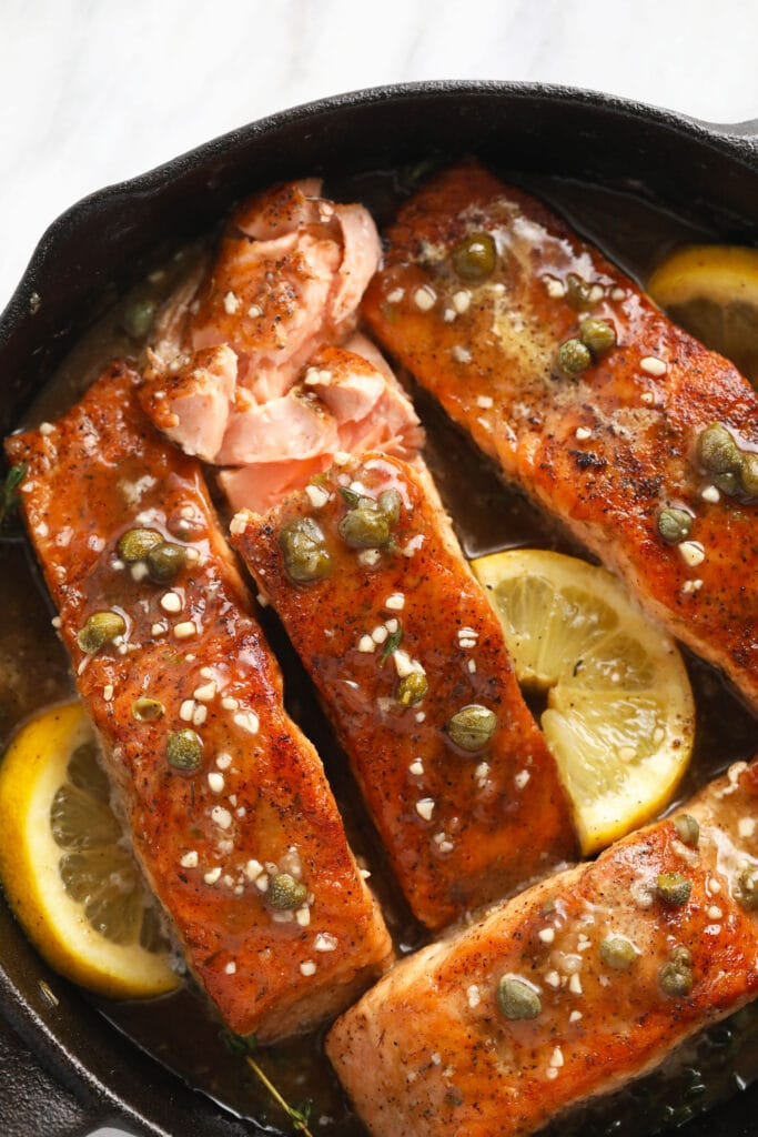 Salmon piccata in a cast iron pan with lemons, capers, and garlic.