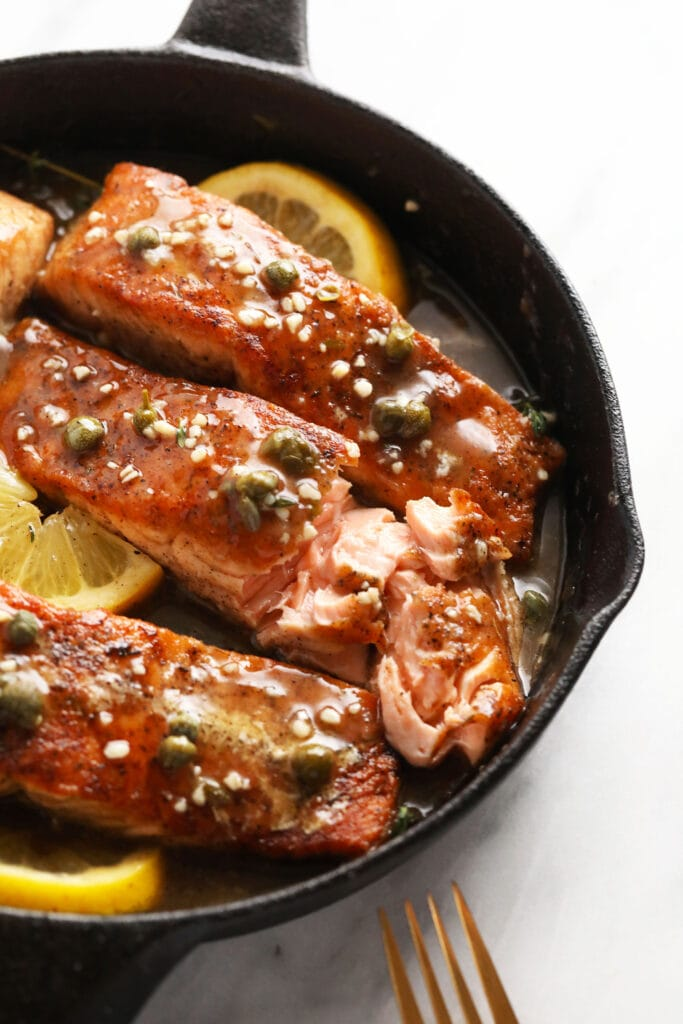 Salmon piccata in a cast iron pan,