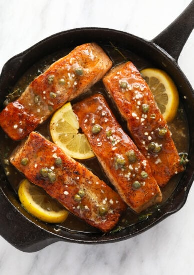 Salmon piccata in a cast iron with lemons, capers, and garlic.