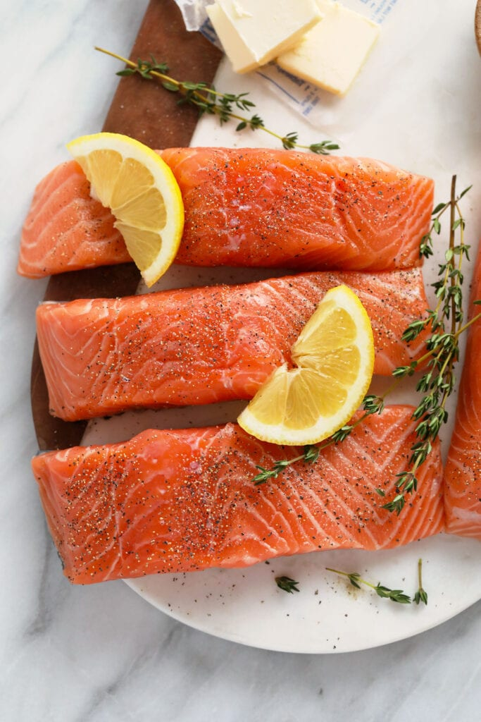 Raw salmon with salt, pepper, fresh lemon, and thyme on a plate.