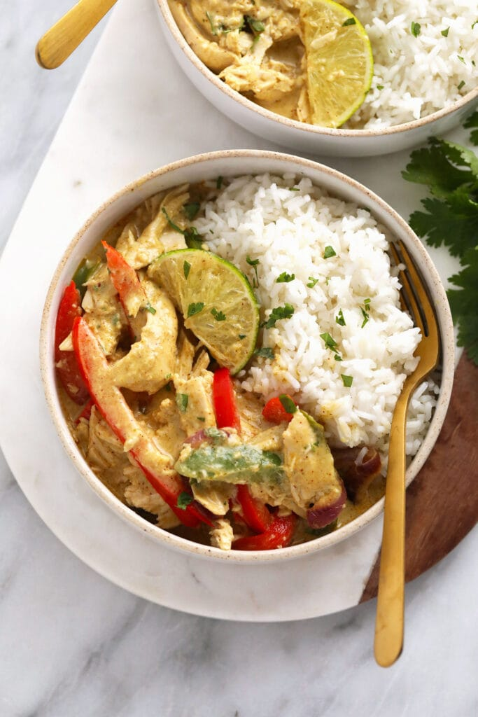 Coconut curry chicken in a bowl with rice, peppers, and onions.