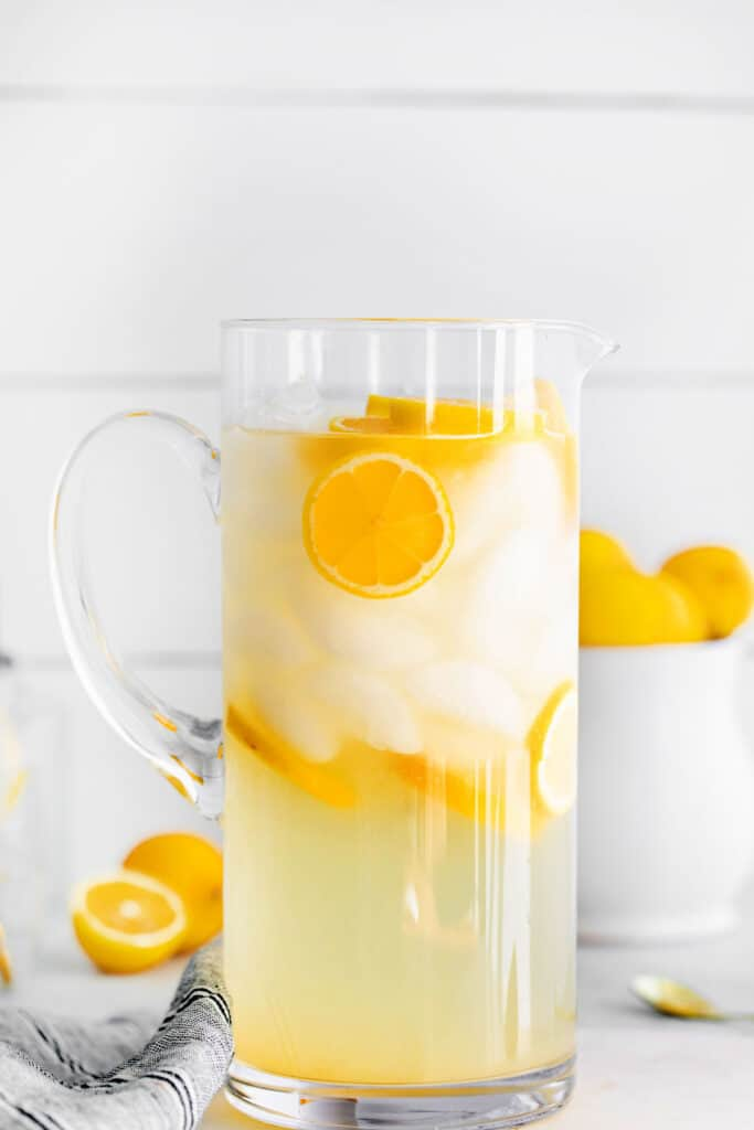 A pitcher of lemonade with ice and lemon slices floating in it.