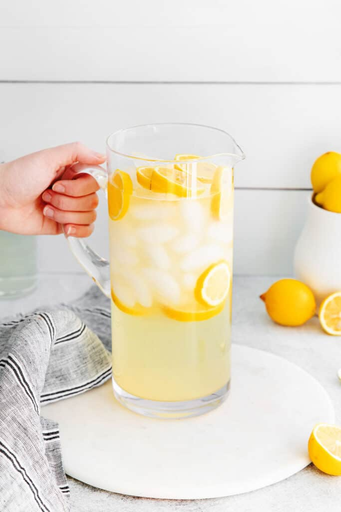 A pitcher of lemonade with ice and slices of lemons.