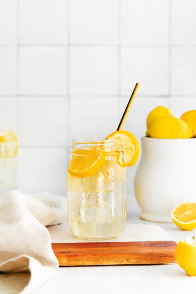 A jar of lemonade with a straw and lemon slices.