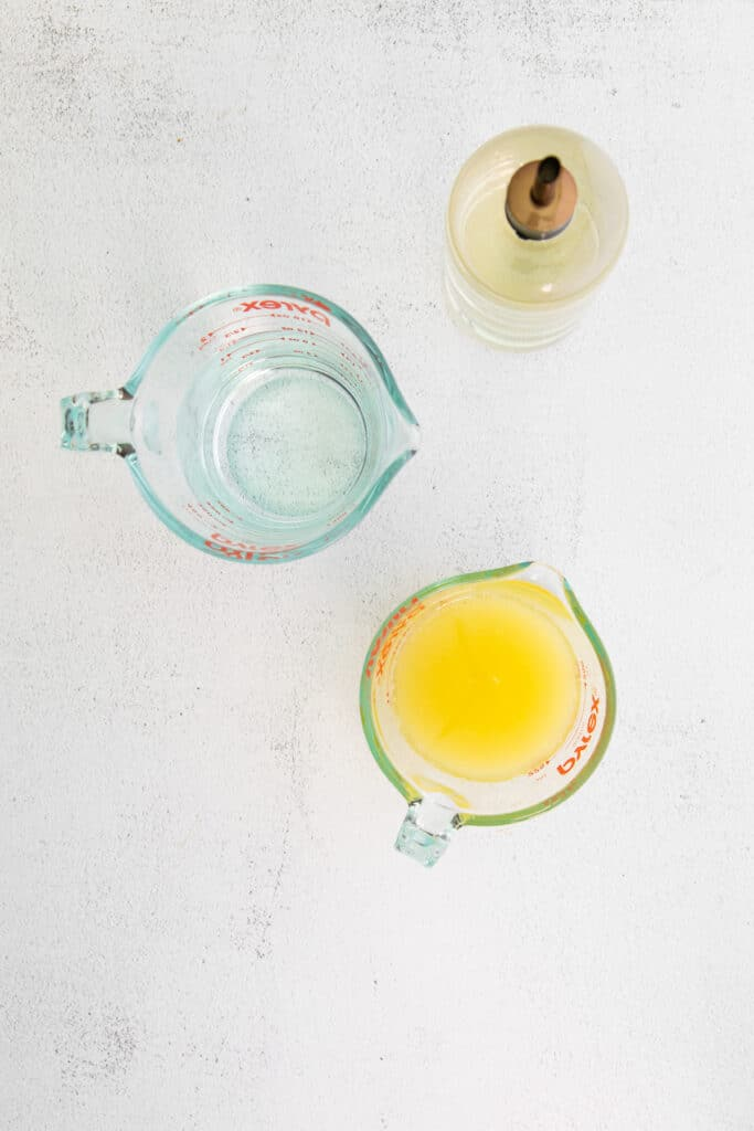 Lemon juice, simple syrup, and water on a counter top.