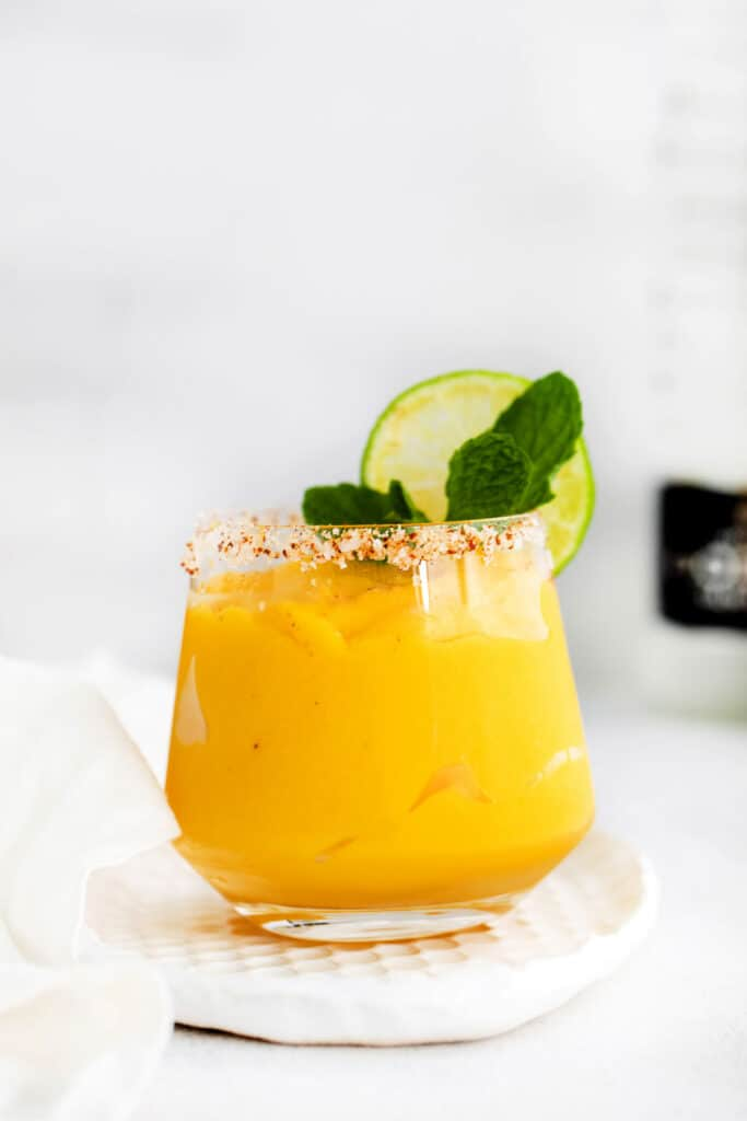 mango margarita in glass with lime
