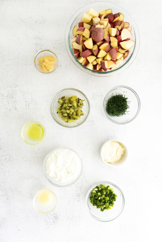 all the ingredients for red potato salad in small bowls.