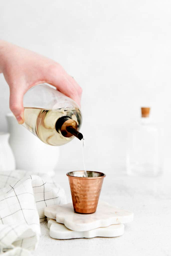 pouring simple syrup into shot glass