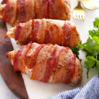 bacon wrapped chicken on cutting board