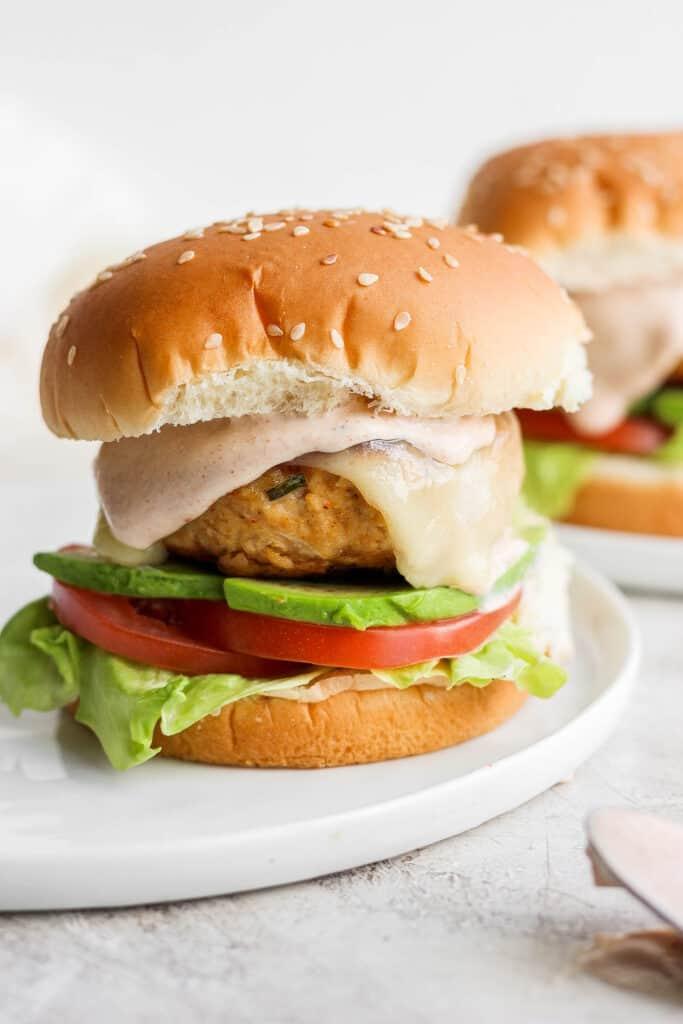 chicken burger on bun with avocado and tomato