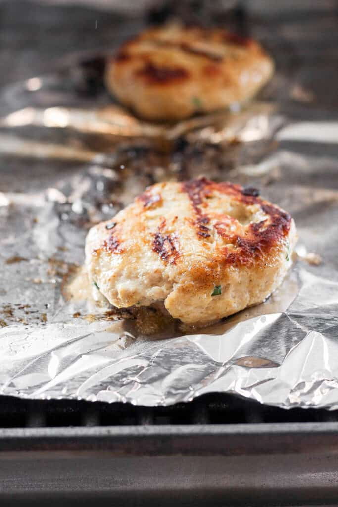 ground chicken burger on tin foil on grill