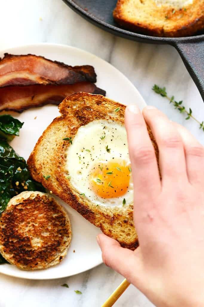 hand holding egg in toast