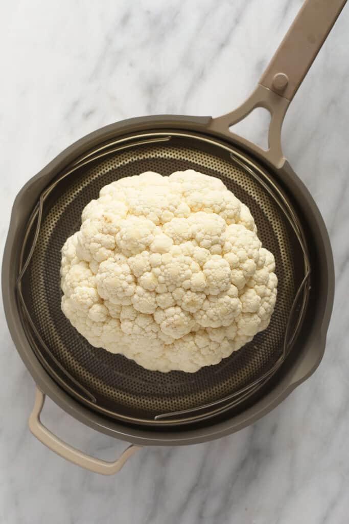 A head of cauliflower in a steamer.