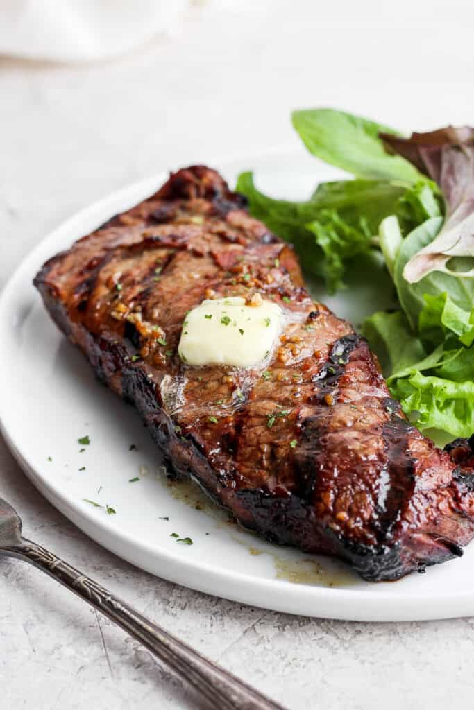 steak on a plate with greens