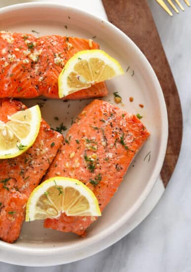 pan seared salmon on plate with fresh lemon and dill