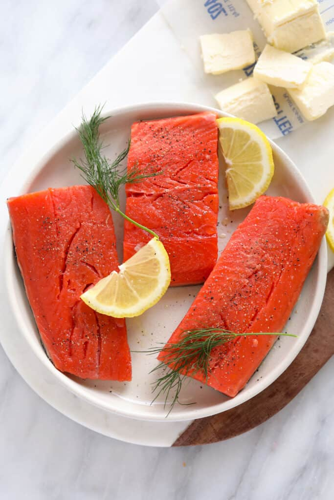 uncooked salmon fillets with lemon and dill on plate