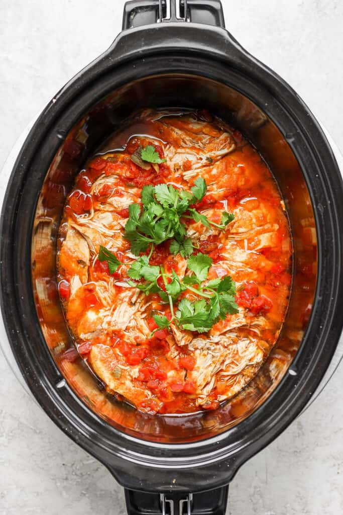 shredded chicken tacos meat with cilantro in slow cooker