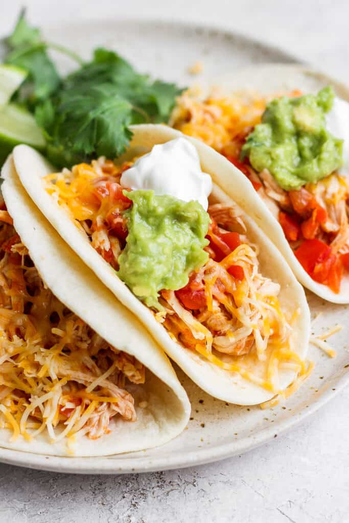 chicken tacos with cheese and guacamole on plate