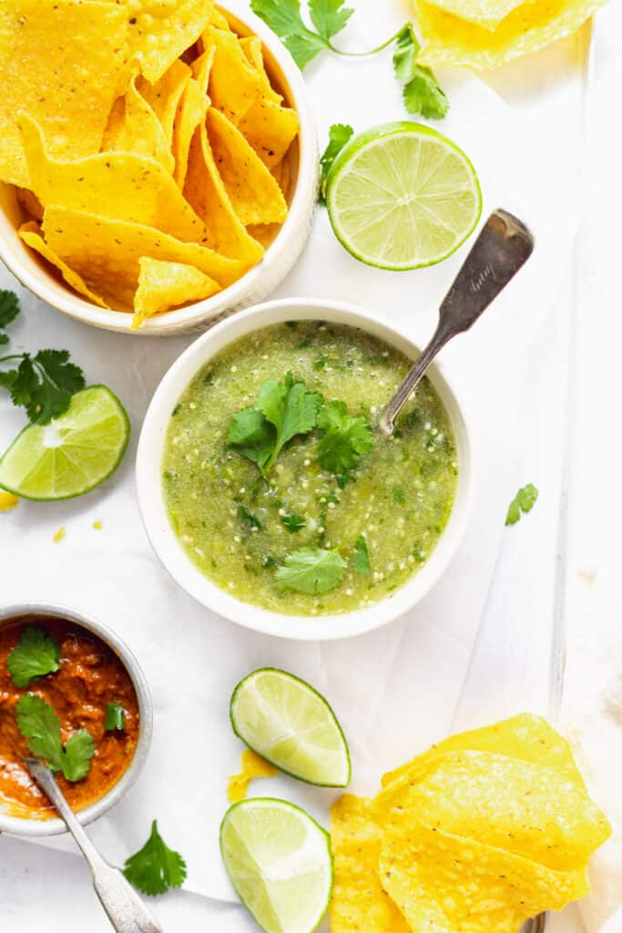 Salsa verde in a bowl surrounded by chips and lime wedges.