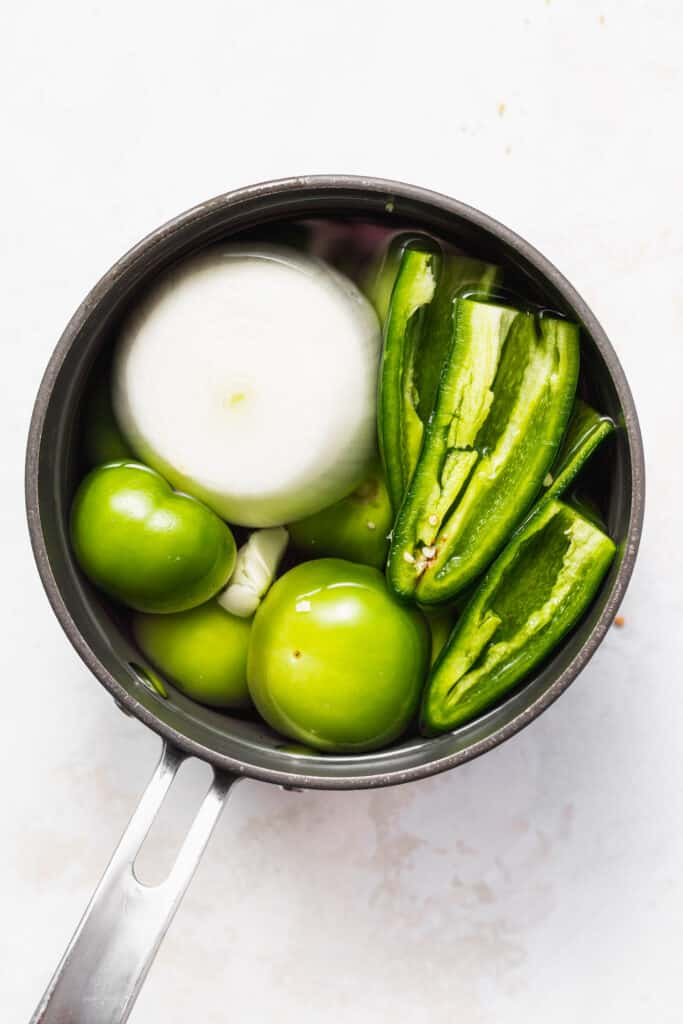 Tomatillos, garlic, onion, jalpeños, and other ingredients in a saucepan.